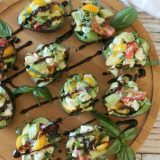 Caprese Stuffed Avocado -Avocados stuffed with fresh mozzarella, garden tomatoes, and basil - drizzled with balsamic glaze and topped with crunchy salt flakes. Perfect summer appetizer or make it a meal with a bed of baby greens and grilled chicken!
