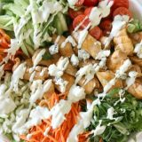 Buffalo Chicken Salad with Blue Cheese Dressing - chicken thighs marinated and glazed in buffalo sauce then baked in the oven. Add your favorite salad vegetables like butter lettuce, matchstick carrots and grape tomatoes. Tossed to perfection with tangy Blue Cheese Dressing, makes an easy summer meal!