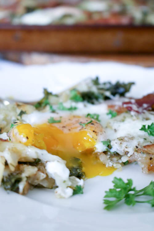 Sheet Pan Breakfast with Kale, Bacon and Hash Browns - Oven-baked, easy and delicious. Baked kale is turned into nutritious crispy chips while hash browns and eggs add comfort to this simple breakfast. Be sure to use pastured bacon so you can reserve the grease for another healthy breakfast. Omit cheese for Whole30 (and it's just as good!) #realfood #sheetpan #breakfast