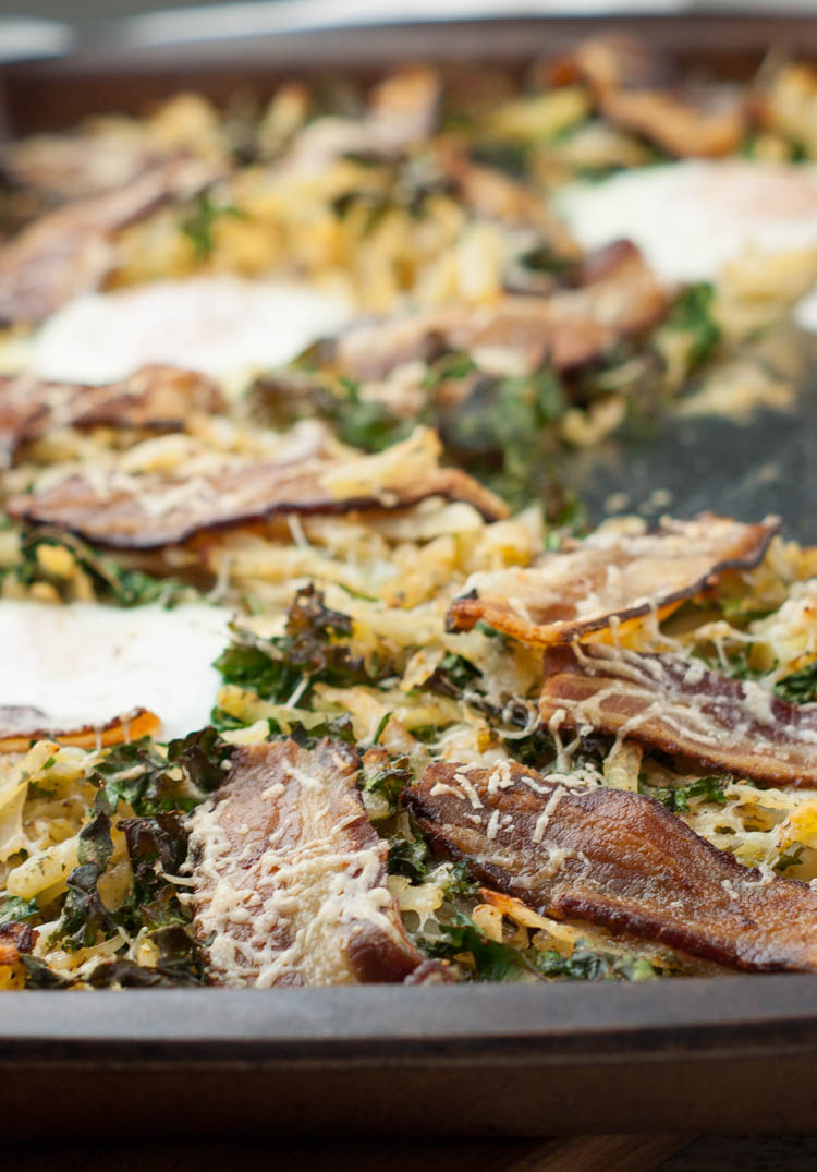 Sheet Pan Breakfast with Kale, Bacon and Hash Browns - Oven-baked, easy and delicious. Baked kale is turned into nutritious crispy chips while hash browns and eggs add comfort to this simple breakfast. Be sure to use pastured bacon so you can reserve the grease for another healthy breakfast. Omit cheese for Whole30 (and it's just as good!) #realfood #cleaneating #breakfast
