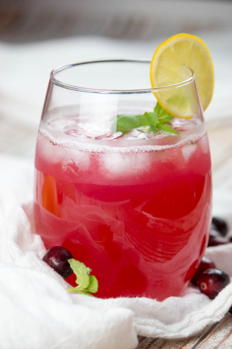 Healthy cranberry juice in a glass with ice and lemon slice