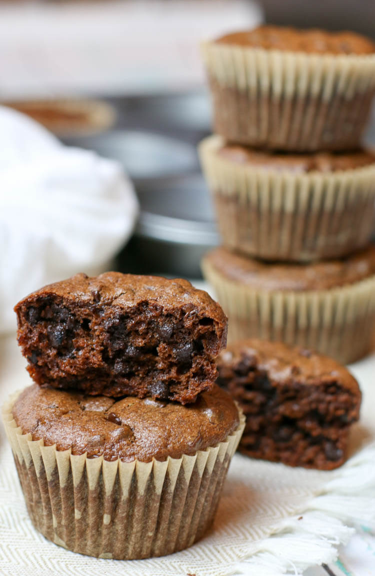 Flourless muffins stacked on top of each other and one is half eaten.