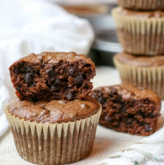 Half eaten double chocolate muffin that is gluten free and sweetened with banana.