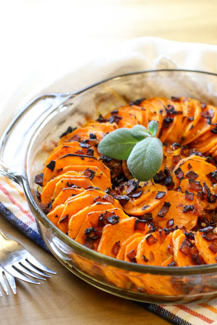 Scalloped sweet potatoes in a clear glass dish with bacon and sage