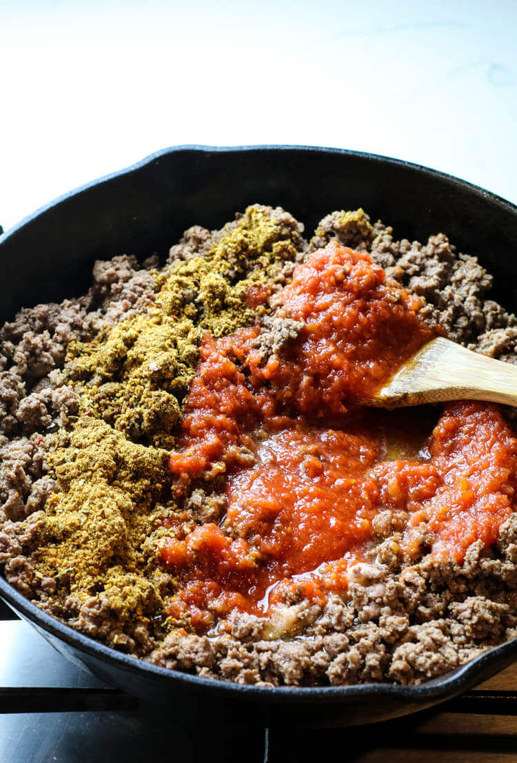 Ground beef on skillet with taco seasoning, salt and tomato sauce.