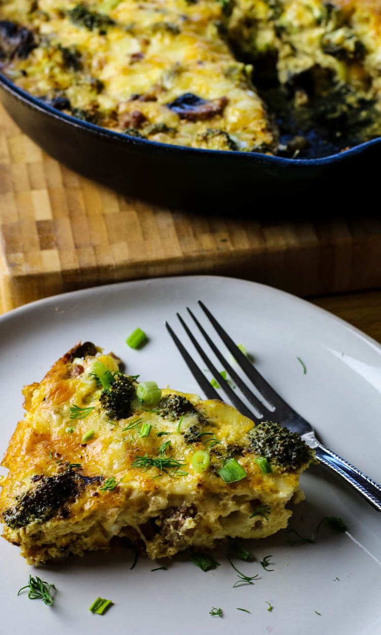 Slice of broccoli frittata on small plate with cast iron pan in the background.