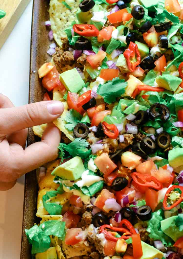 Sheet pan nachos with tortilla chips, taco meat and toppings.