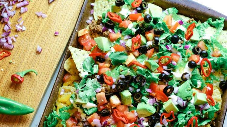 Loaded nachos on sheet pan with diced onions and jalapenos.