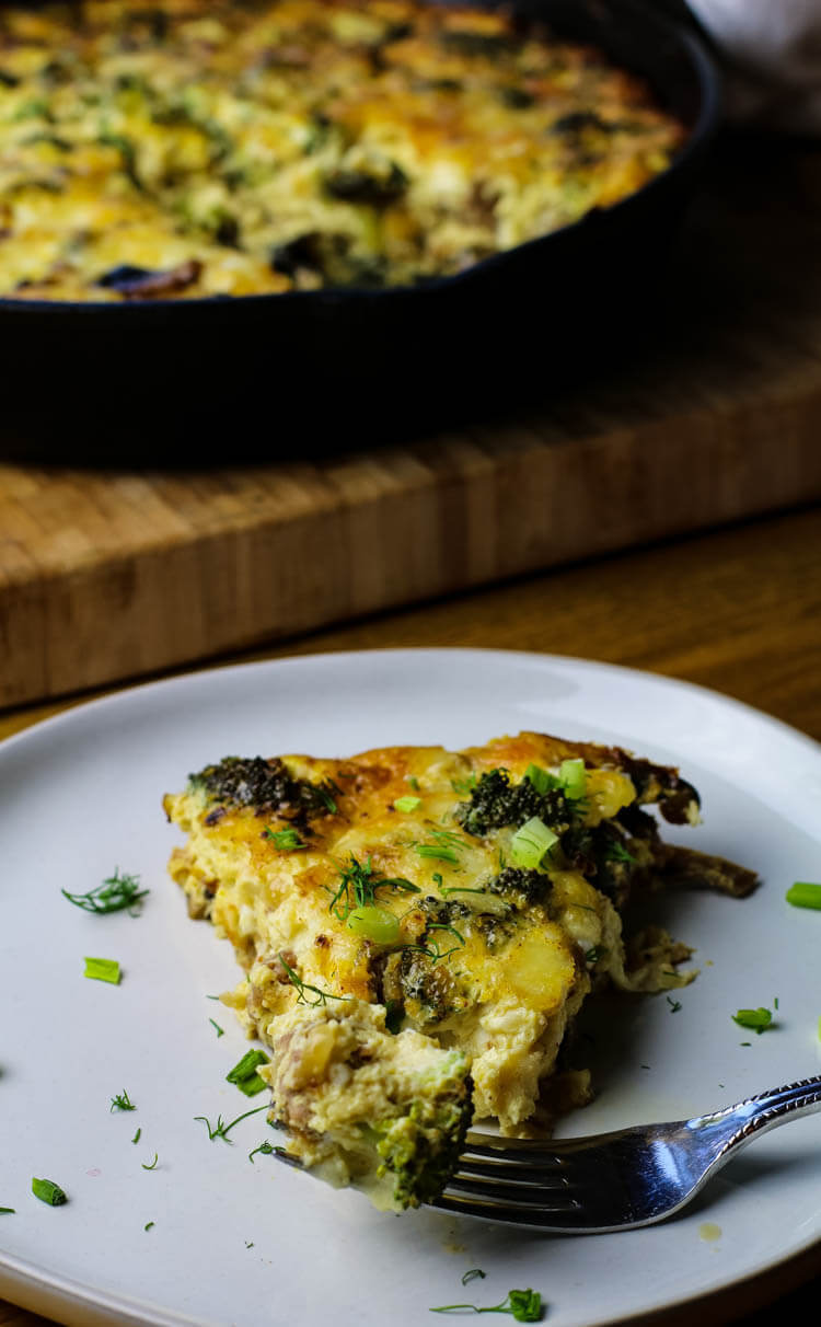 A slice of egg and sausage frittata on a white plate with cast iron pan in the background.