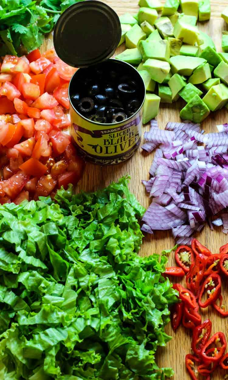 Toppings for nachos - lettuce, tomatoes, onions, avocado, cilantro, and jalapeno.