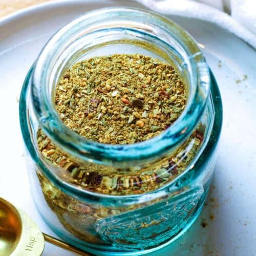 Taco Seasoning in a small jar. Specks of garlic and onions and oregano visible.