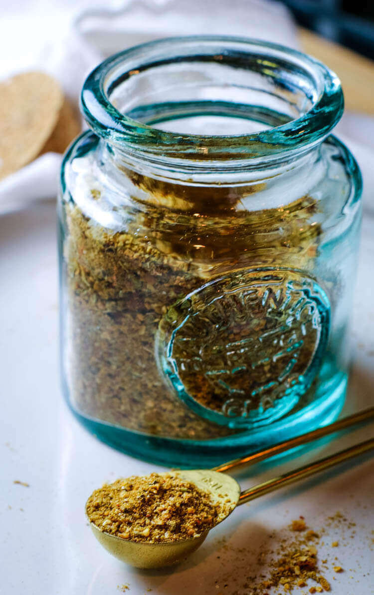 Taco Seasoning in a small blue jar with a spoonful of the mixture.