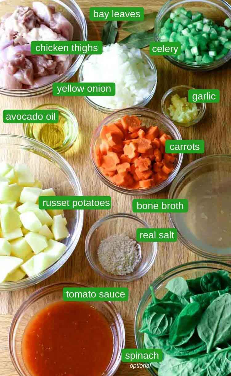 Chicken stew ingredients such as potatoes, celery, onions, carrots, bone broth, tomato sauce and spinach.