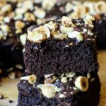 Two slices of coconut flour brownies with hazelnuts on top.