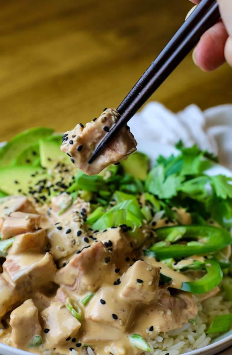 Piece of salmon in creamy sriracha mayo poke sauce with chopsticks.