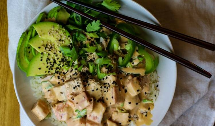 Creamy salmon poke with sliced avocado, greens and topped with sesame seeds.
