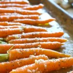 Small carrots on a baking sheet with garlic chunks.