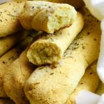 Low carb bread sticks seasoning with Italian seasoning and garlic salt. One bread stick is broken in half to expose the crumbly and chewy texture of the bread sticks.