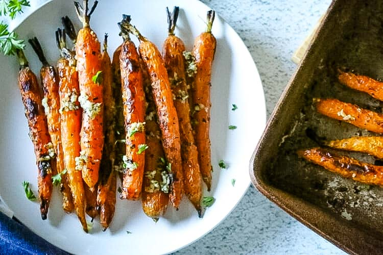 Carrots roasted in the oven on a small white plate with baking sheet next to it.