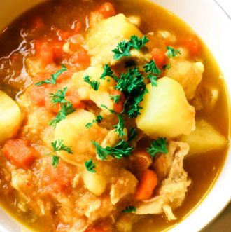 White bowl of chicken stew with potatoes and veggies.