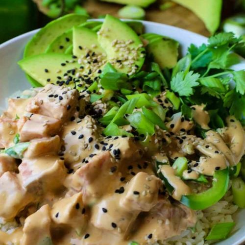 Salmon poke in a white bowl on a bed of white rice with avocado, cilantro and green onions topped.