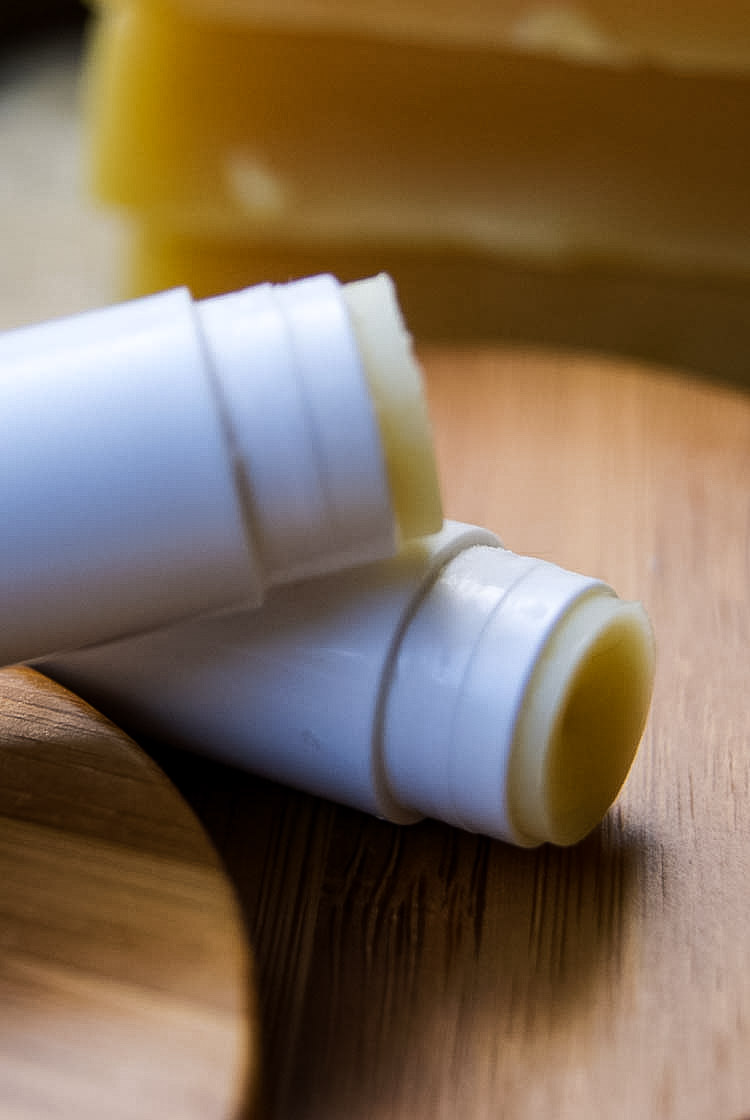 Homemade lip balm (2 tubes) that are opened on a bamboo cutting board with beeswax bricks in the background.