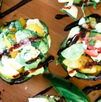 Caprese Stuffed Avocados with mozzarella and grape tomatoes and fresh basil.