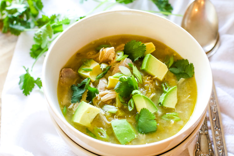 Chicken chili with healthy toppings like avocado, cilantro, green onions
