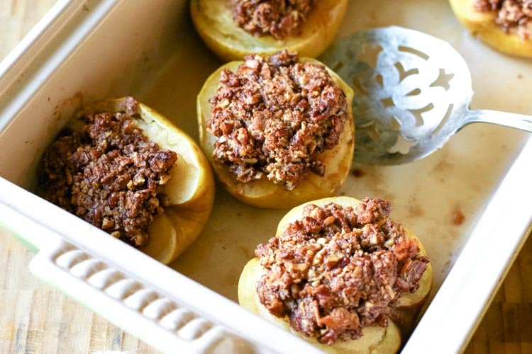 Baked apple halves with pecan crumble and slotted spoon