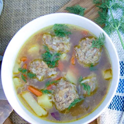 meatball soup in a white bowl with fresh dill