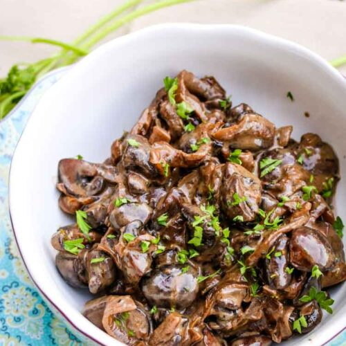 Creamed mushrooms with onions and red wine in a small serving bowl