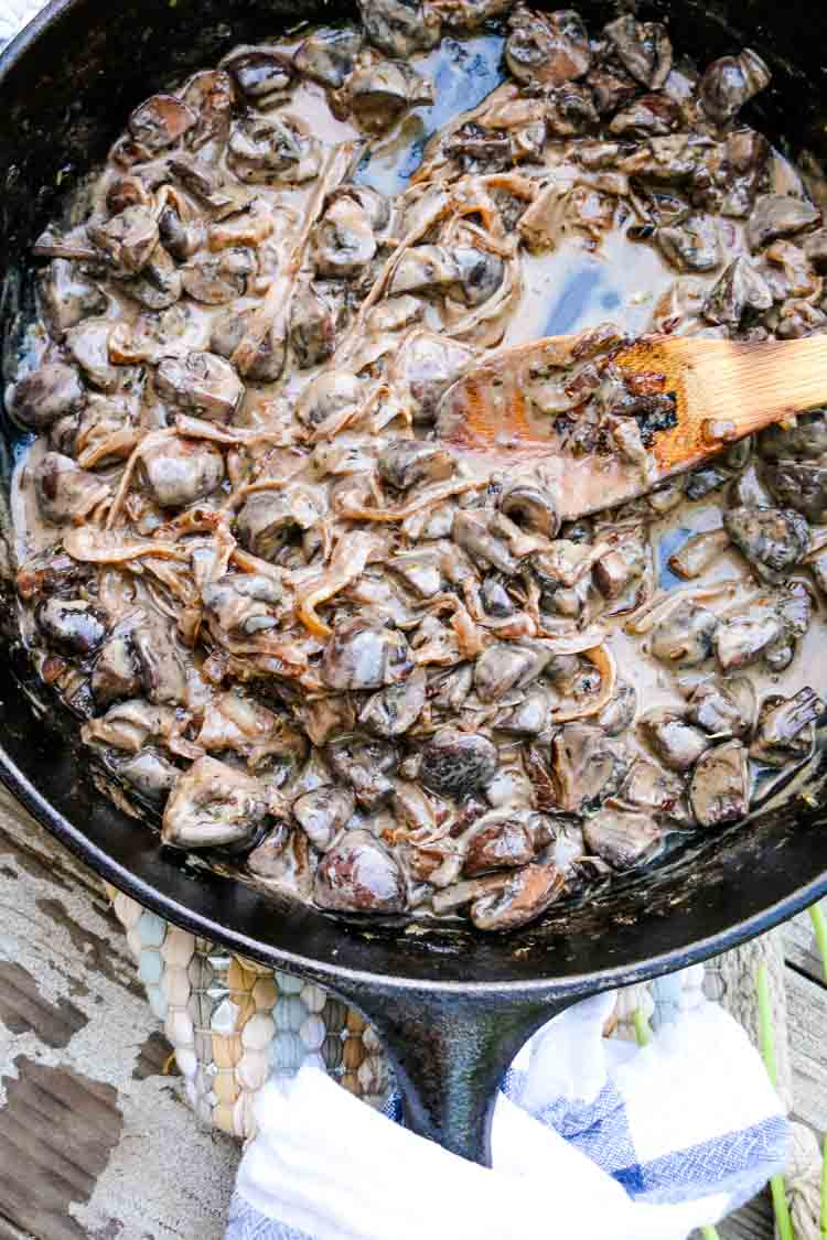 Creamed mushrooms in a cast iron skillet on a wooden table