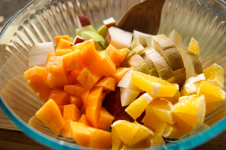 Fall fruits like persimmon, oranges, pears in a mixing bowl with wooden spoon