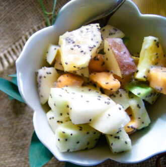 Fall fruits in a small white bowl with yogurt dressing and chia seeds