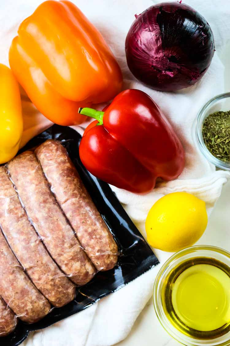 Ingredients for Sausage and Peppers Sheet Pan: sausages, bell peppers, red onion, lemon, oil and seasonings