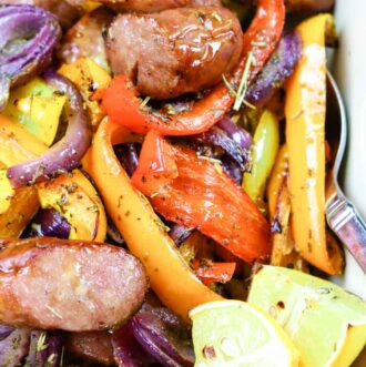 Baked in the oven sausages, bell peppers, onions, and lemon wedges