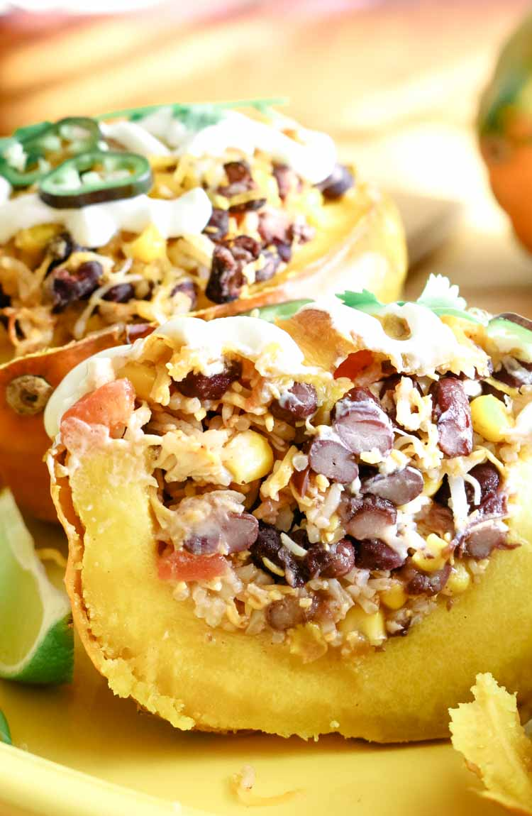 Rice, beans and corn stuffed acorn squash cut in half to expose stuffing.