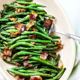 Green beans with bacon on a platter with a serving spoon