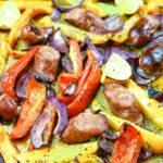 Red, orange and yellow bell peppers with sausage and red onions on a sheet pan