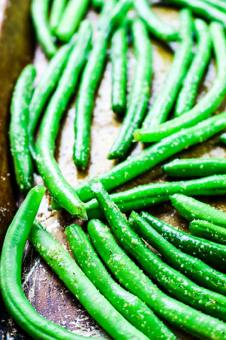 Seasoned raw green beans on a sheet pan