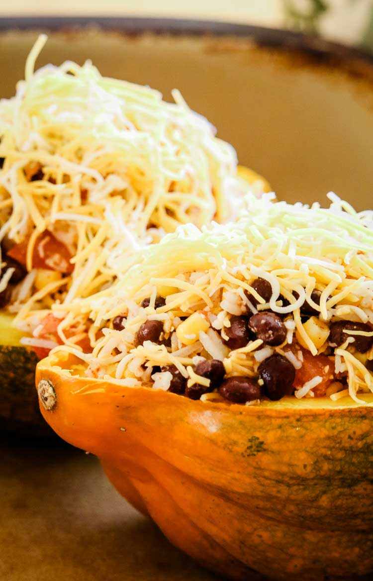 Stuffed Acorn Squash ready to go into the oven, topped with Mexican cheese blend.