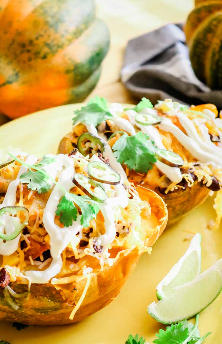 Mexican Stuffed Acorn Squash with sour cream and cilantro and lime wedges as garnish.