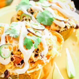 Roasted and Stuffed Acorn Squash with drizzle of sour cream, cilantro and jalapeno