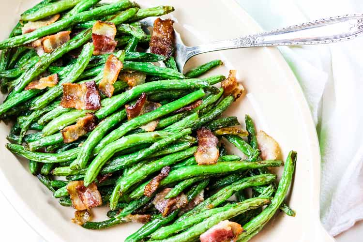 Green beans with crunchy bacon pieces in a serving platter