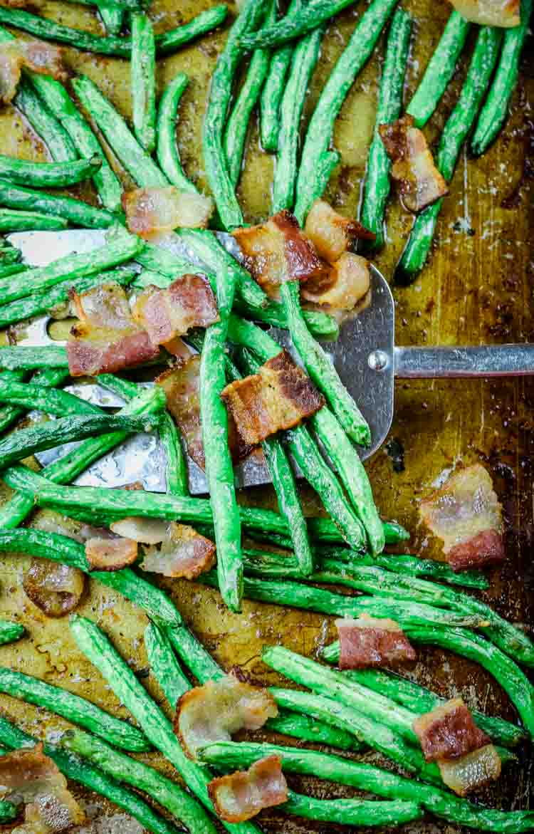 Oven raosted green beans and crunchy bacon on sheet pan with spatula
