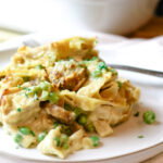 white plate with fork and single serving size of tuna casserole with peas and mushrooms