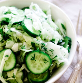 white bowl with sliced cucumbers, shredded cabbage and two forks off to the side