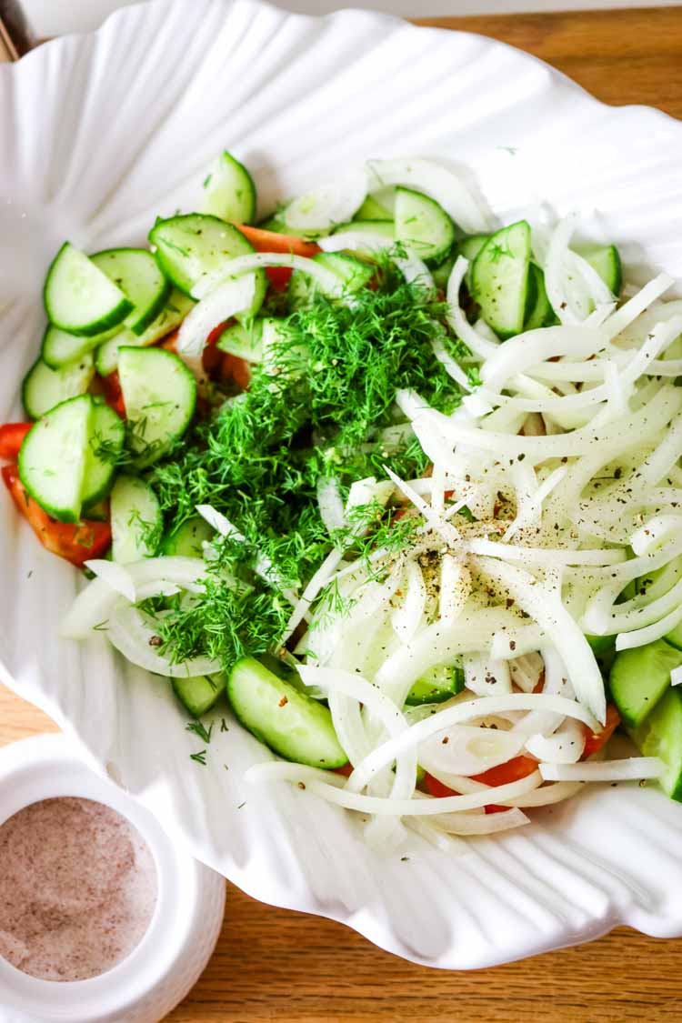Sliced cucumbers, thinly sliced onions, and tomato wedges in a white bowl