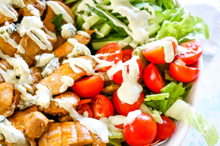 Creamy blue cheese dressing drizzled over buffalo chicken dressing