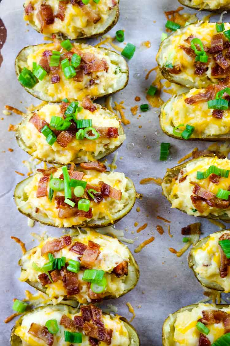 Baked loaded potatoes with bacon and green onions on a baking sheet